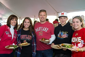Photo of 5 family members holding plates of food and wearing Maryland shirts and hats