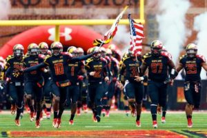 Maryland football team running on field in black uniforms carrying the American flag